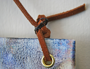 Upper corner of piece with leather cord as hanger